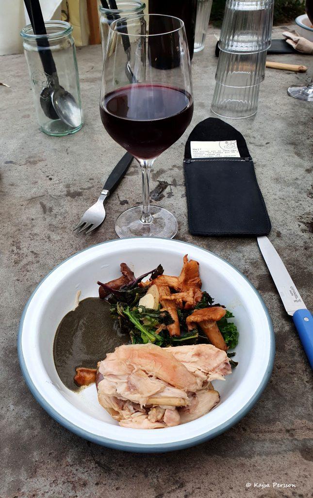 Vit plåttallrik med en portion med grillad kanin, grillad kål med kantareller och en grön grankåddasås. Ett glas rött vin och den svarta läderbörsen vid sidan av
