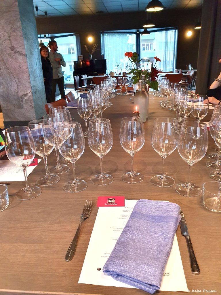 Uppdukat bord med vinglas för en vinprovning. Fem glas på varje plats med en beskrivning av kvällens viner och ostar framför och en blå tygservett