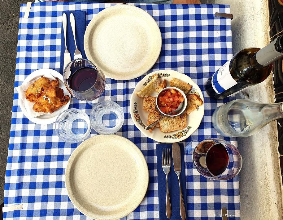 Lunch tallrikar på en blå vit rutig duk med vin